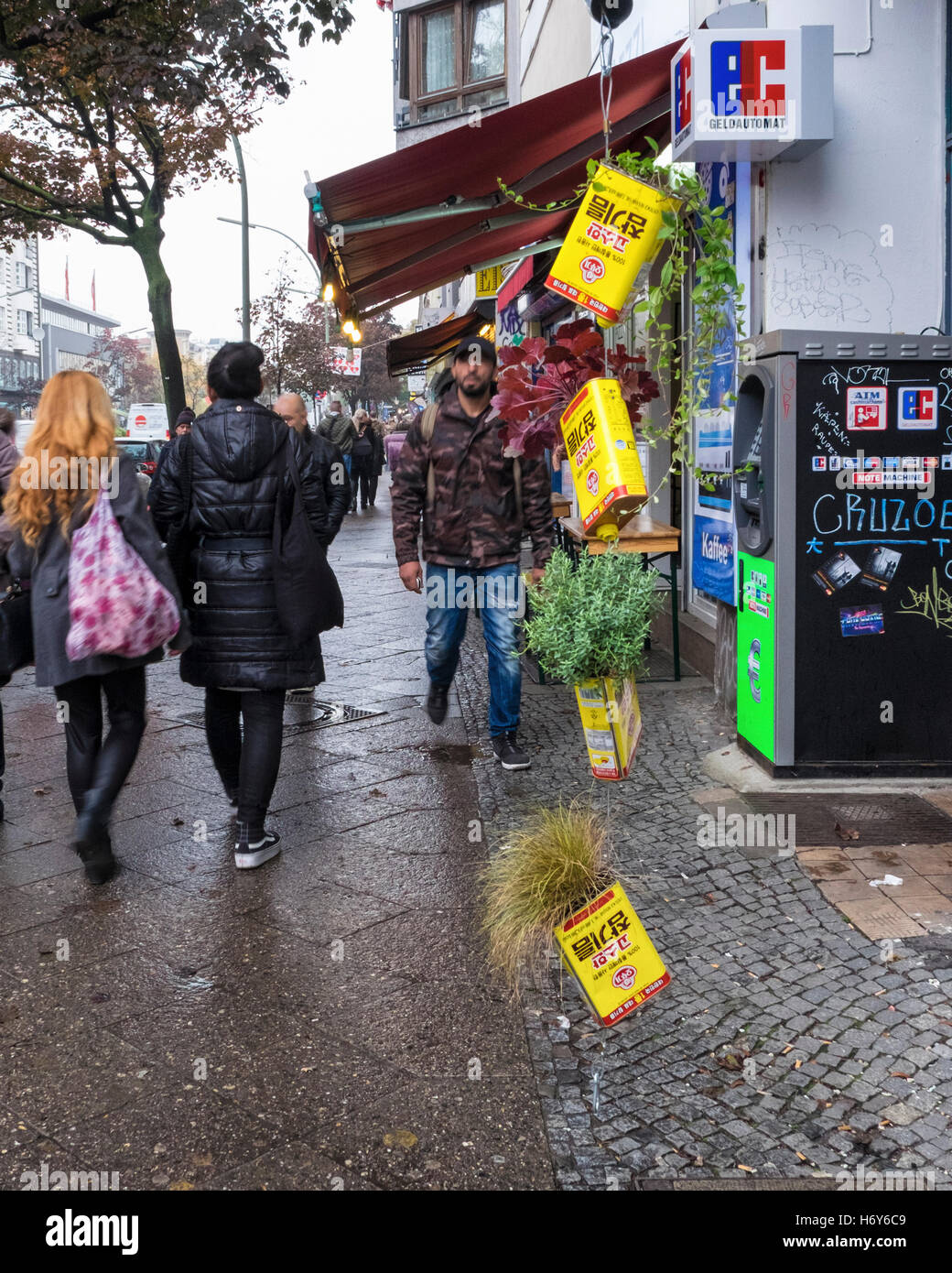 Unusual plant containers, planters. Quirky empty Sesame oil cans hold plants on a city street, Kreuzberg, Berlin - Stock Image