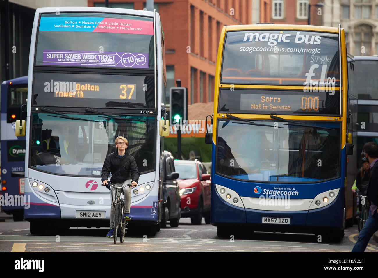 Manchester cyclist stopped at lights bike  First Stagecoach Magic bus buses competition privatised not in service - Stock Image