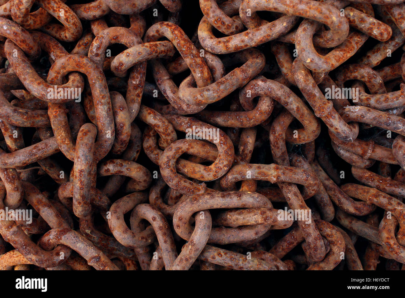 Rusted old iron chains background as a stack of oxidized decaying metal links as an abstract symbol of industrial - Stock Image