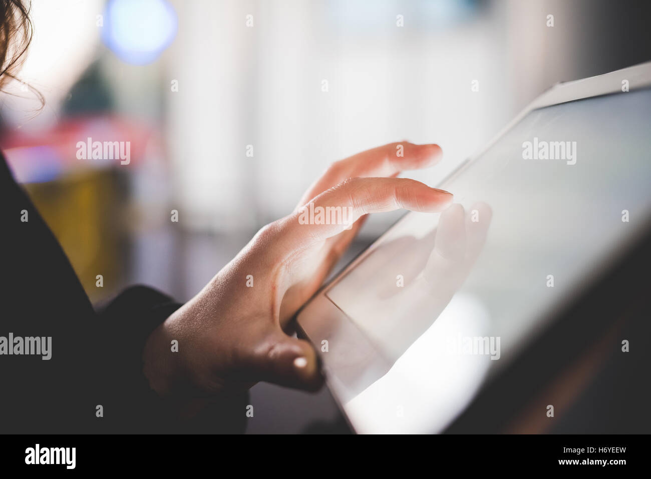 Close up on the hand of young woman using tablet illuminated by screen - Stock Image