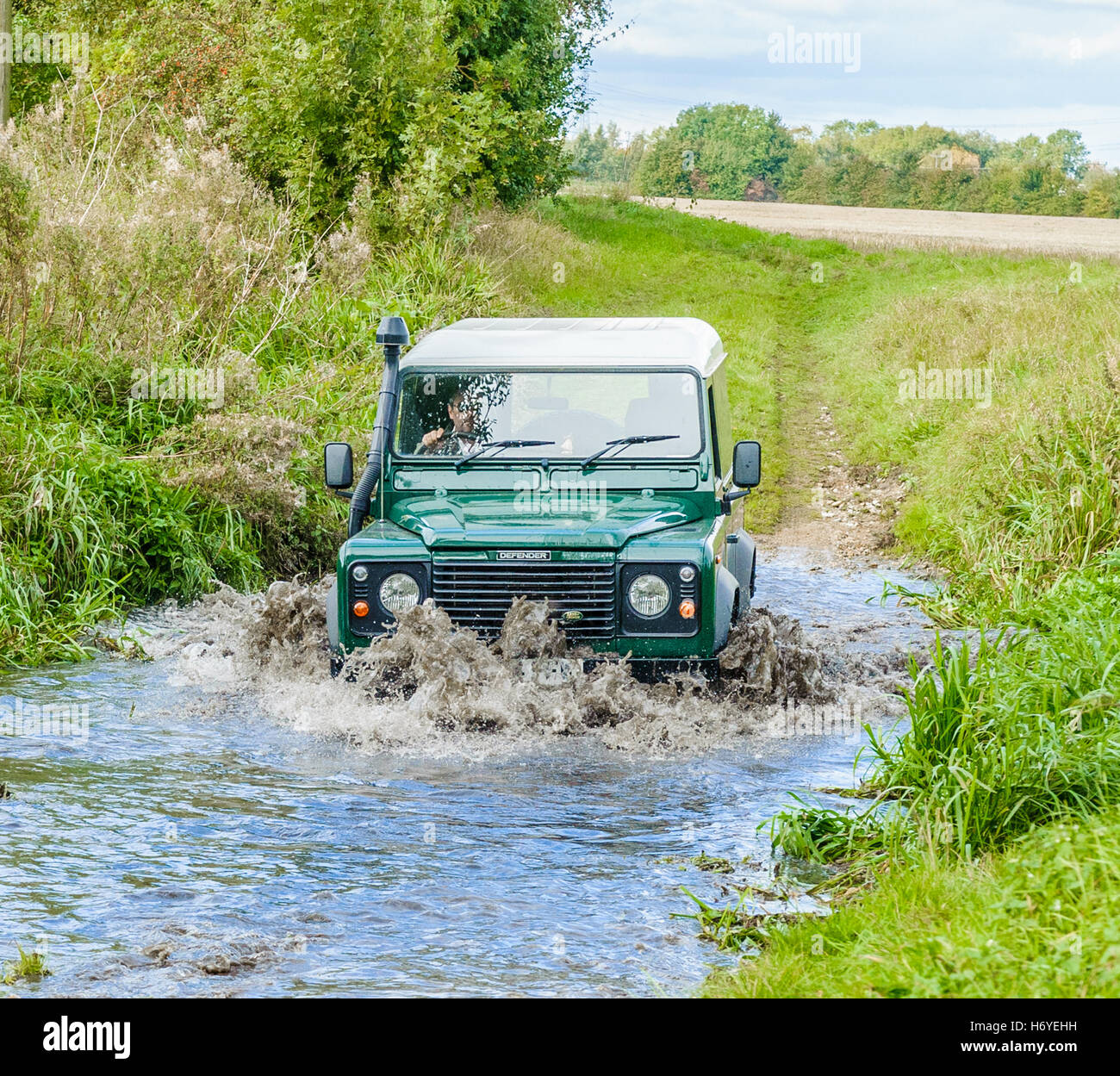 A Landrover Defender 90 crossing, or fording, a stream or river - Stock Image