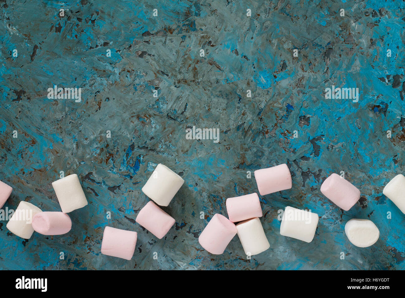 White and pink marshmallows in a ceramic bowl on blue concrete background. View from above. - Stock Image
