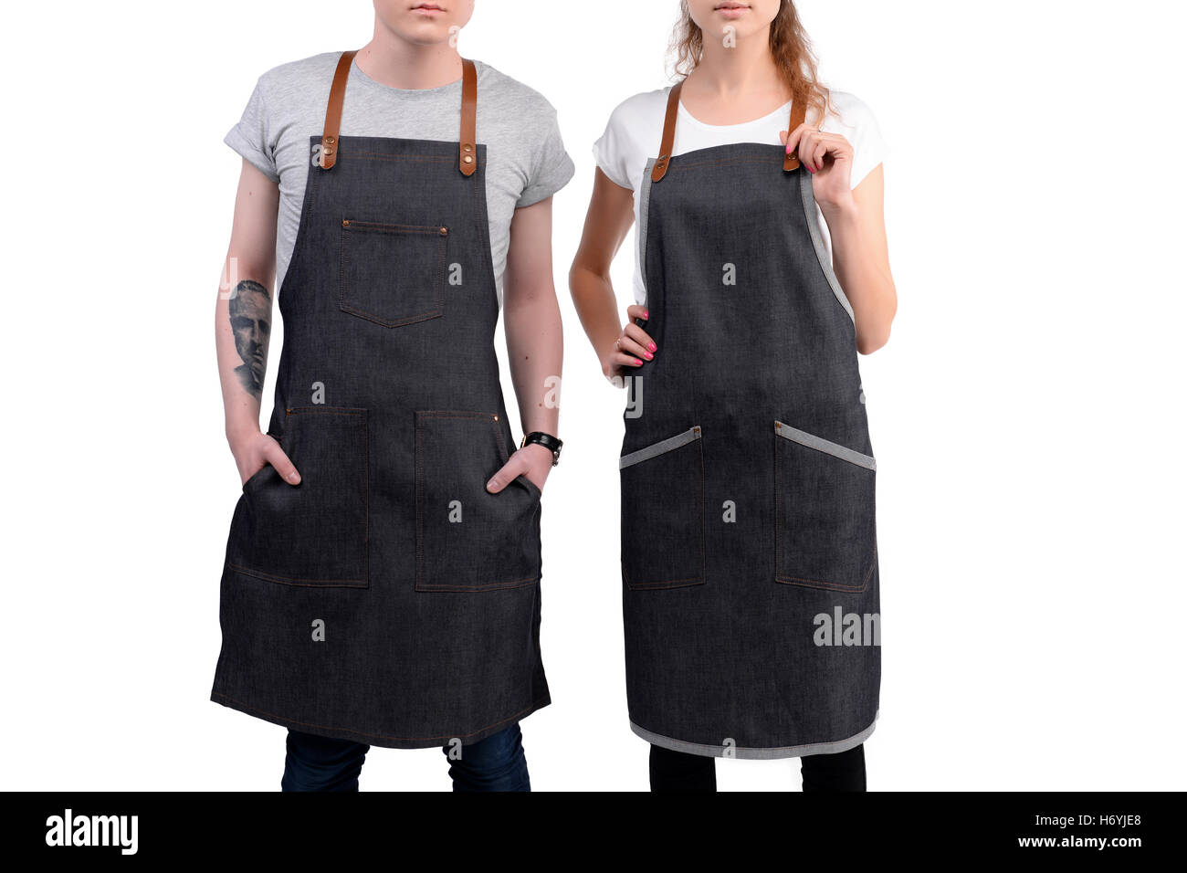 Young chefs or waiters man and woman posing, wearing aprons isolated on white background. - Stock Image