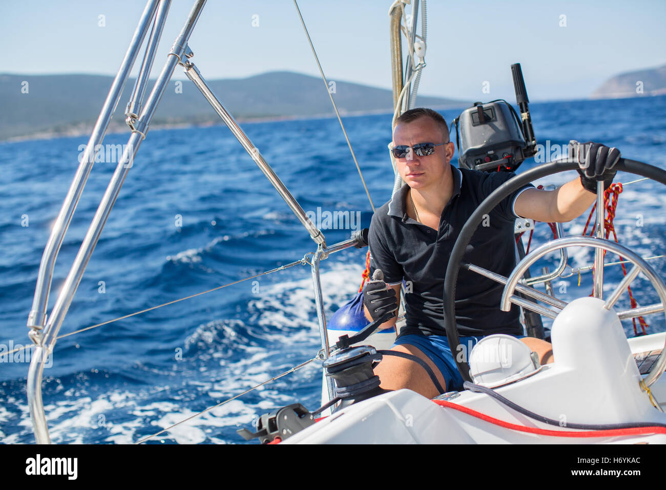 Young man steers a sailing yacht boat in the open sea. Stock Photo