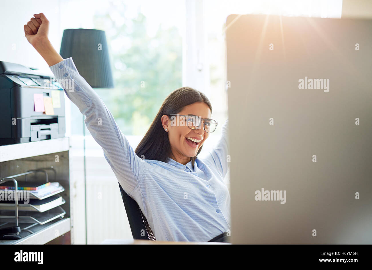 Joyous female entrepreneur in small office with extended arms as if to celebrate something wonderful such as a business - Stock Image