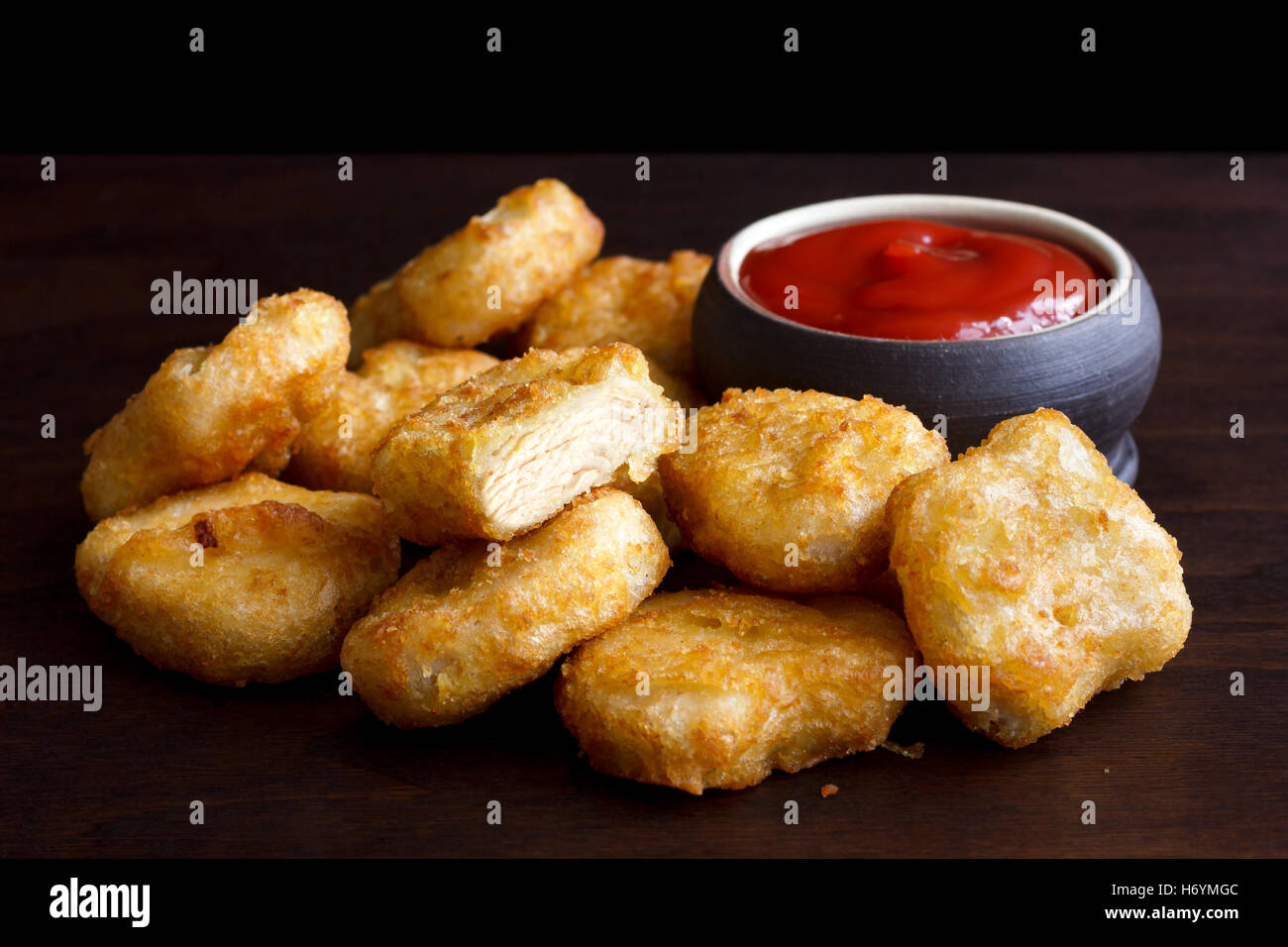 Pile of golden deep-fried battered chicken nuggets with empty rustic bowl on dark wood. One cut with meat showing. - Stock Image