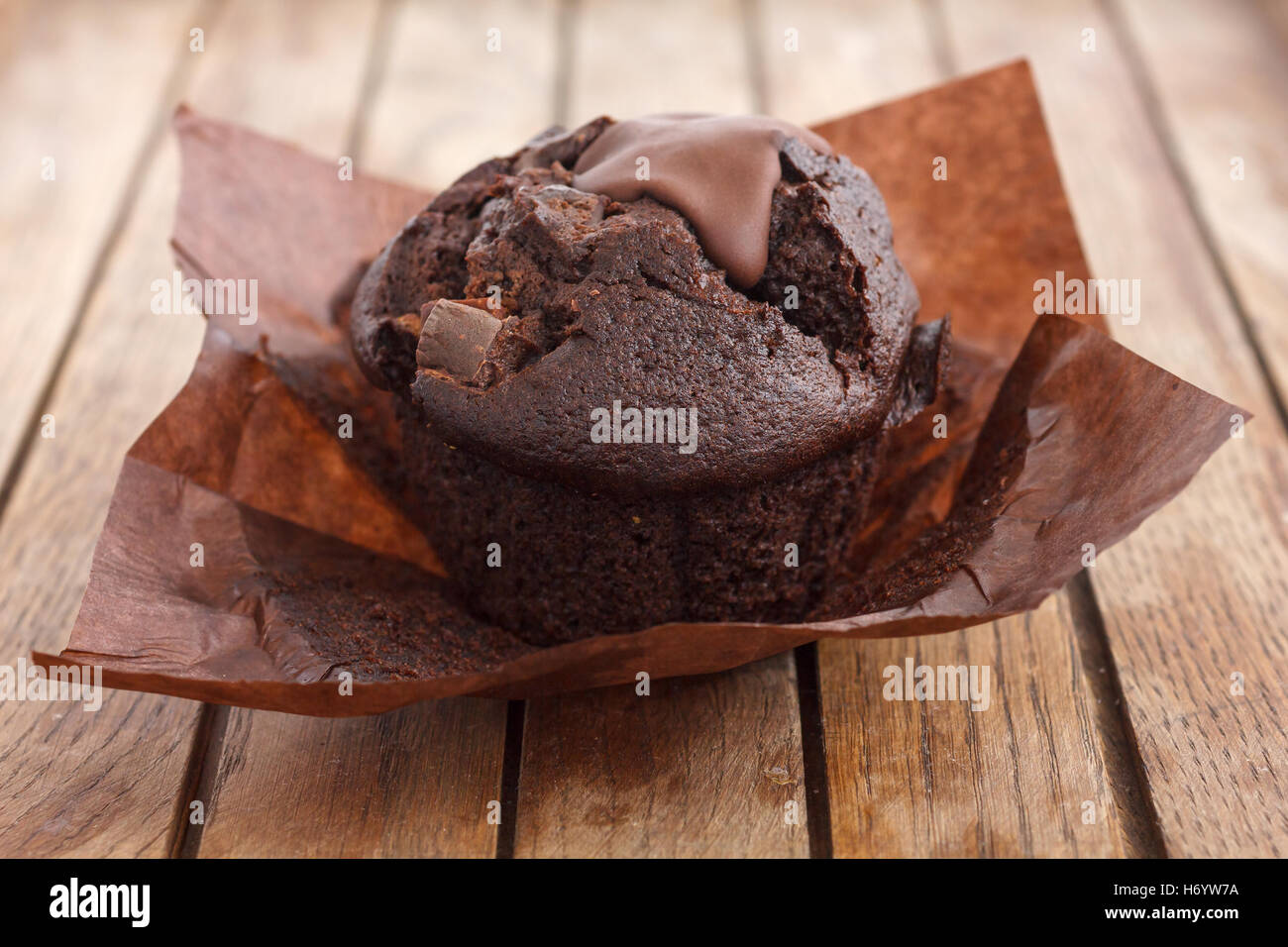 Chocolate chip muffin in brown wax paper. Unwrapped. Stock Photo