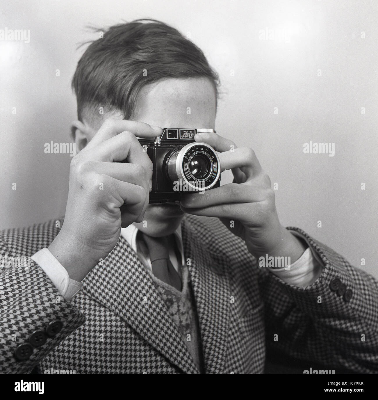 1950s, historical, England, UK, young man wearing a check jacket with tie, taking a hand-held picture with an Italian - Stock Image