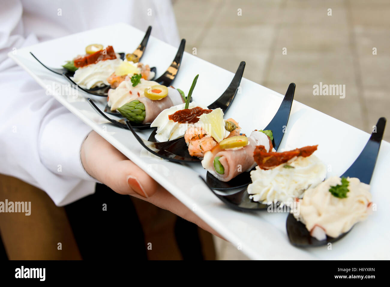Detail of waiter holding canapes on plastic spoons. - Stock Image