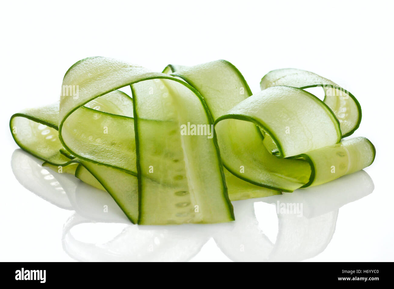 Shaved cucumber strips on white - Stock Image