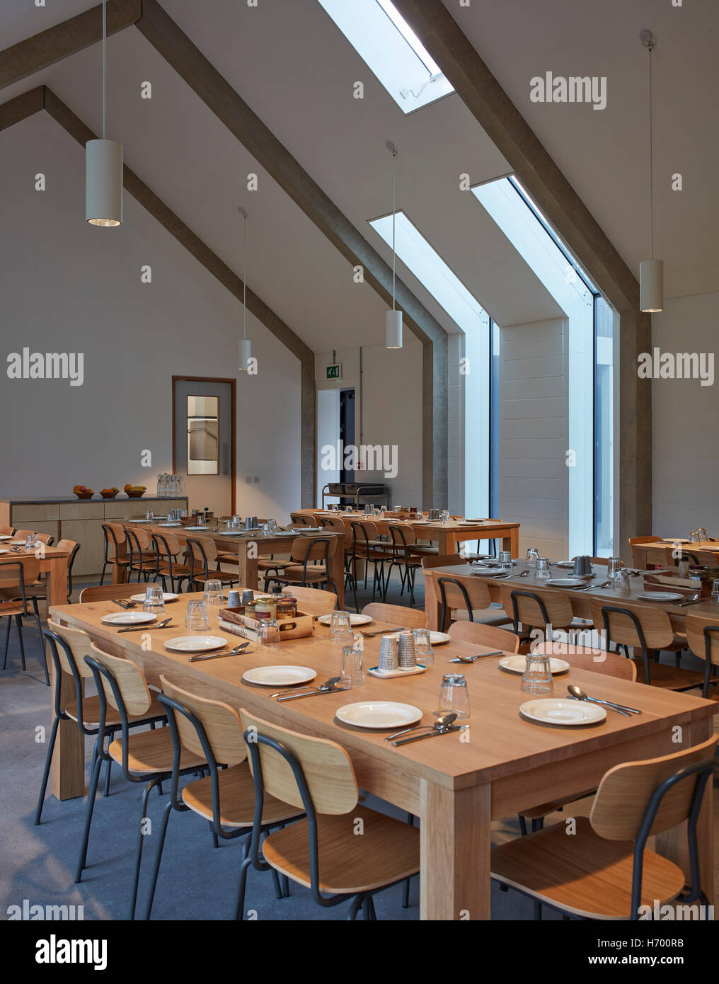 Communal dining room with exposed concrete ribcage. Vajrasana Stock ...