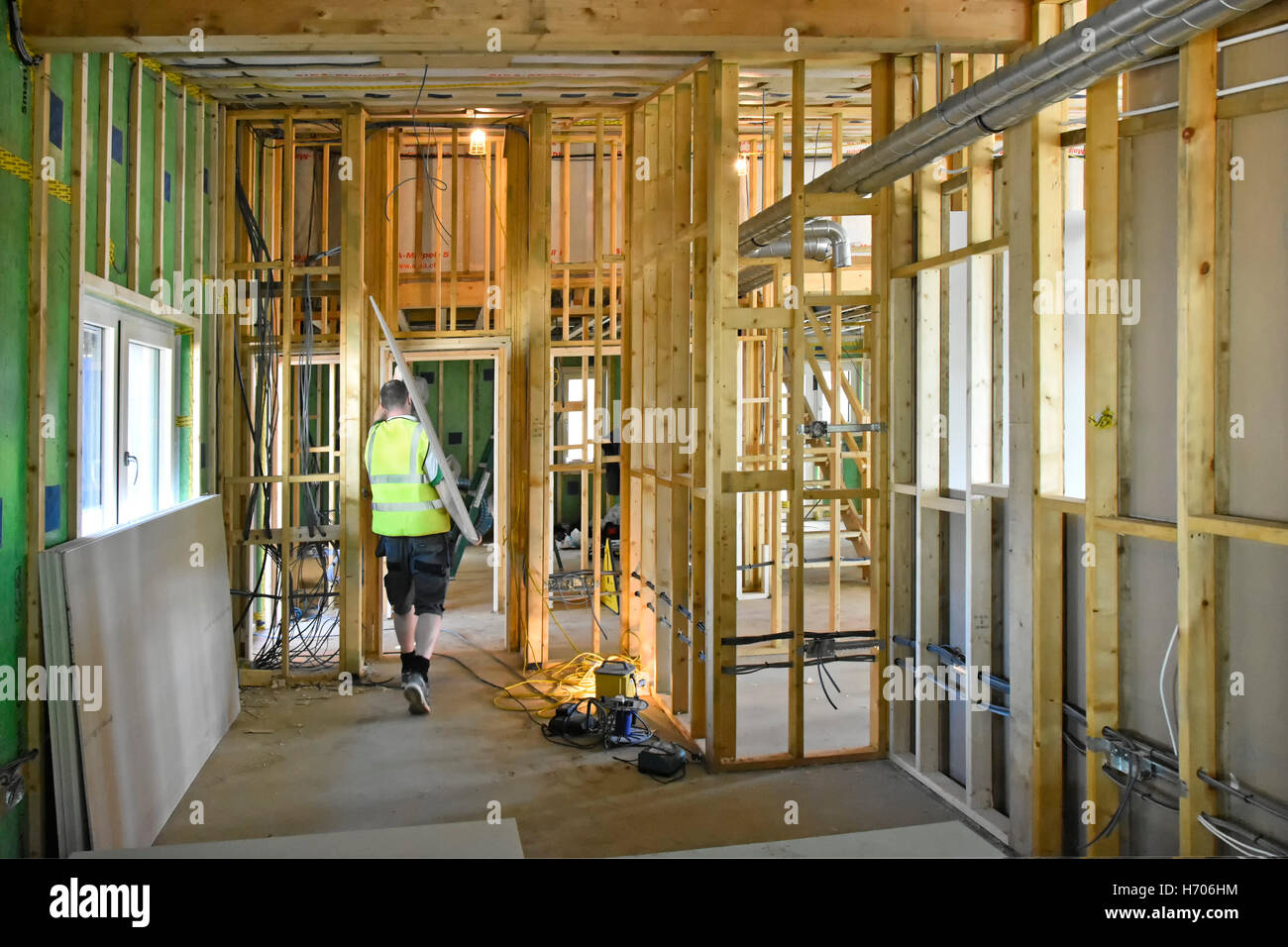 Interior of new UK energy efficient Passive House showing ducting electrics & timber stud partition wall worker - Stock Image