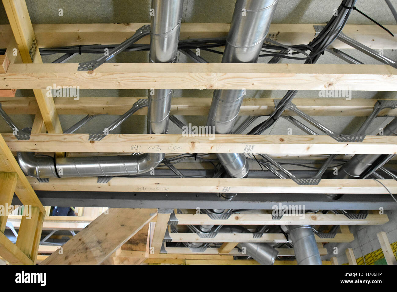 Interior of new UK energy efficient Passive House showing building materials & ventilation trunking installed - Stock Image
