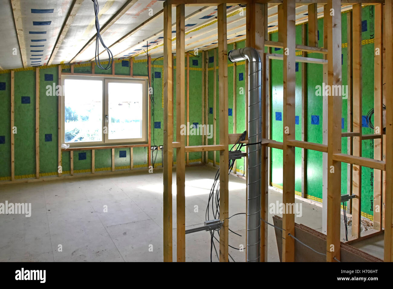 Insulated external walls of timber framed UK Passive House blue patches sealing holes used to pump insulation behind - Stock Image
