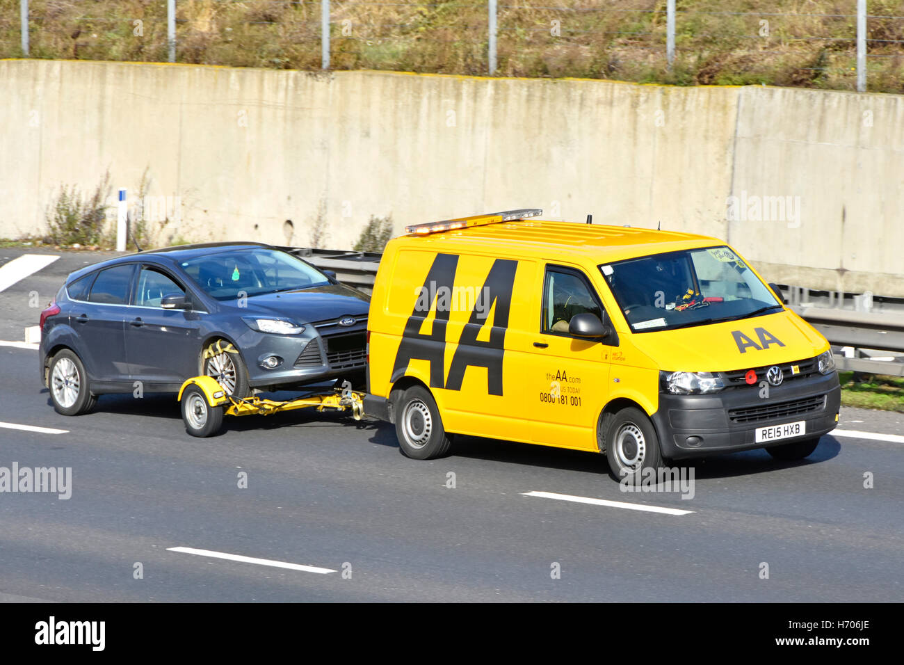 Broken down Ford car being towed along M25 motorway by yellow AA Volkswagen breakdown van with red remembrance poppy - Stock Image