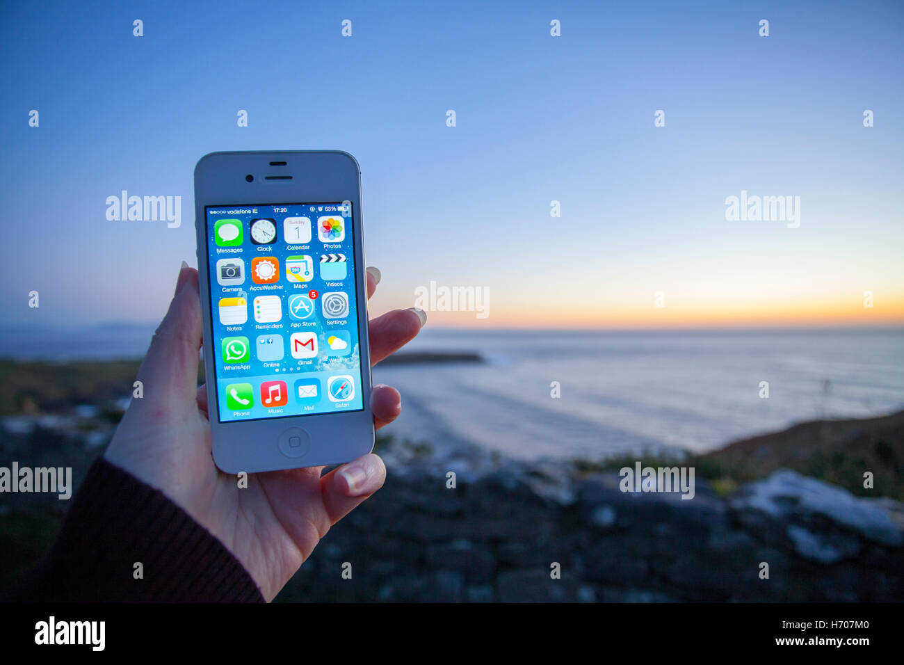 Hands using a smart phone to take a photograph of a landscape at twilight - Stock Image