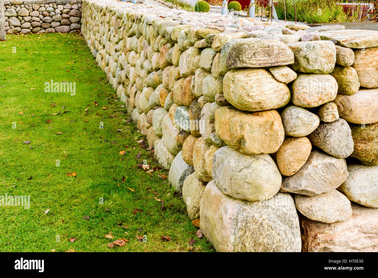 Smooth and well built stone wall with green grass on one side. - Stock Image