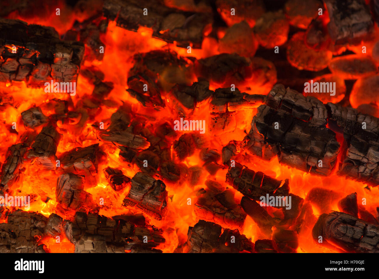 Orange burning smoulder charcoal texture in a barbeque oven - Stock Image