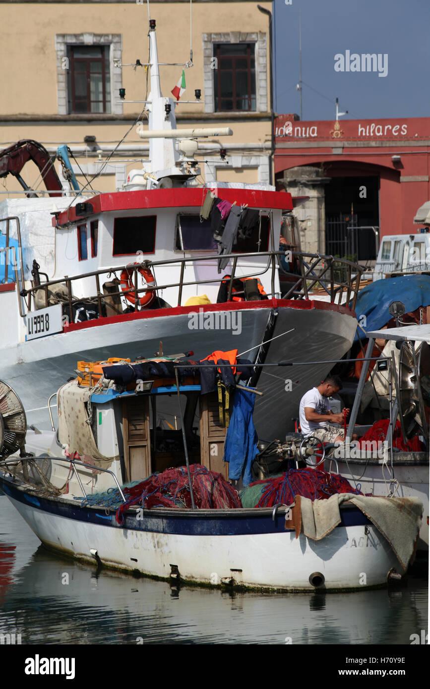 Fisherman repairing nets on boat, Port of Livorno, Italy - Stock Image