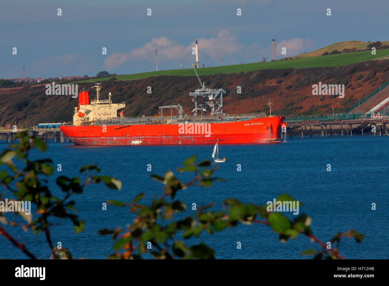 The 'Iris Victoria' berthed at an oil jetty with crew seen against the hill which the oil is pumped up to - Stock Image