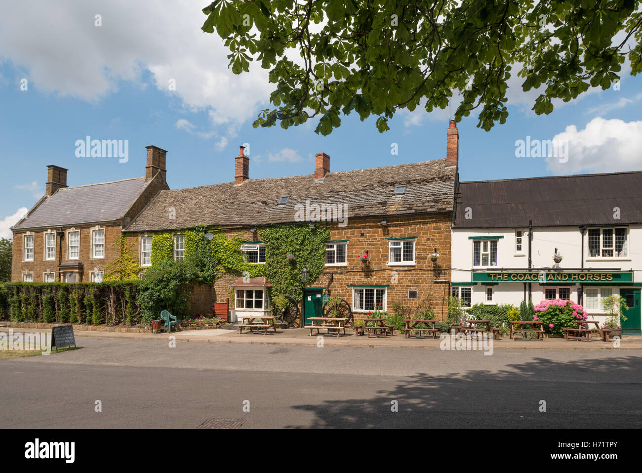 The Coach and Horses (right) and property in the village of Adderbury, North Oxfordshire, England, UK - Stock Image
