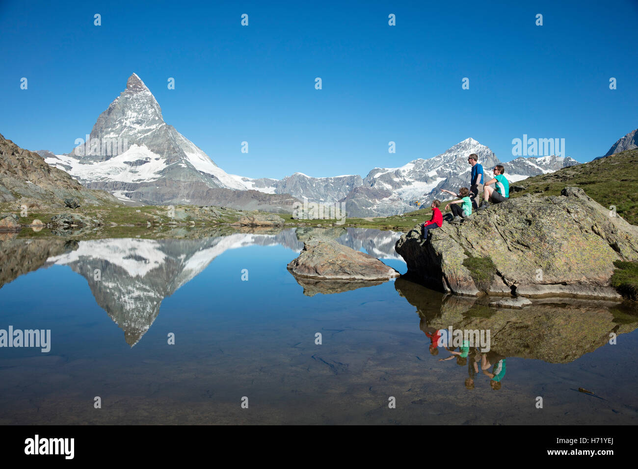 Hiking family and Matterhorn reflected in the Riffelsee. Zermatt, Pennine Alps, Valais, Switzerland. - Stock Image