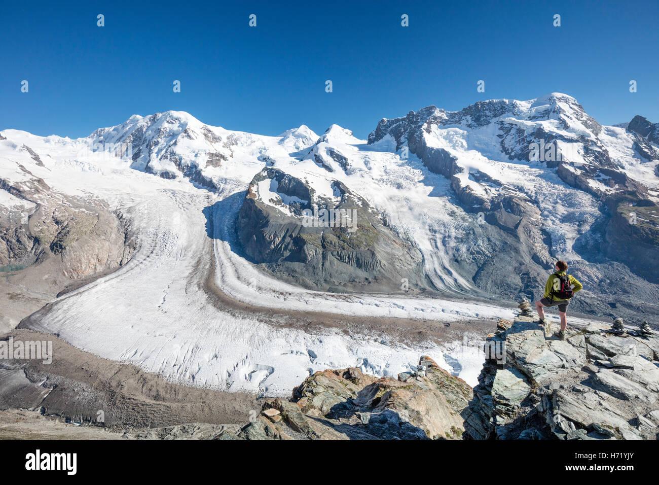 Hiker looking over Gorner Glacier and Monte Rosa from Gornergrat. Zermatt, Pennine Alps, Valais, Switzerland. - Stock Image