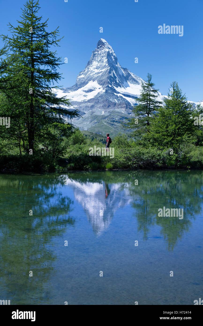 Hiker and Matterhorn reflected in the Grunsee, Zermatt, Pennine Alps, Valais, Switzerland. - Stock Image