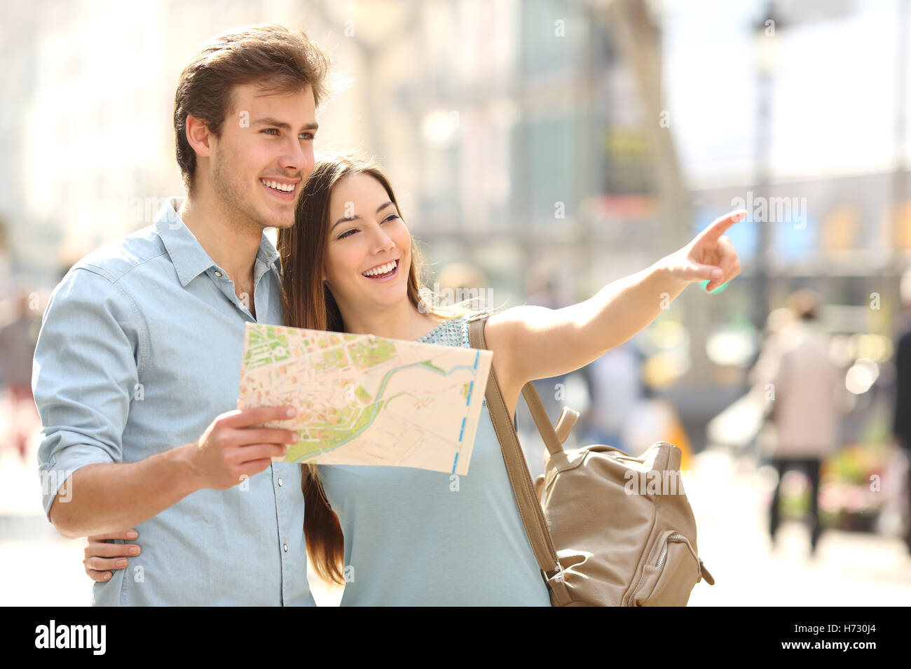 Couple of tourists consulting a city guide searching locations - Stock Image