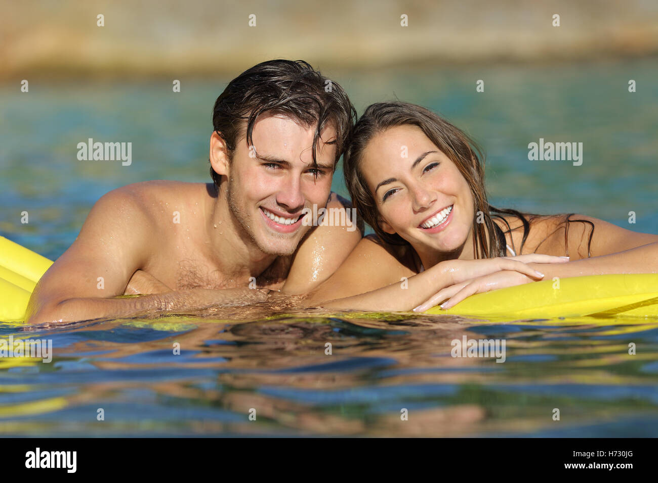 Happy couple bathing on the beach in summer vacation - Stock Image