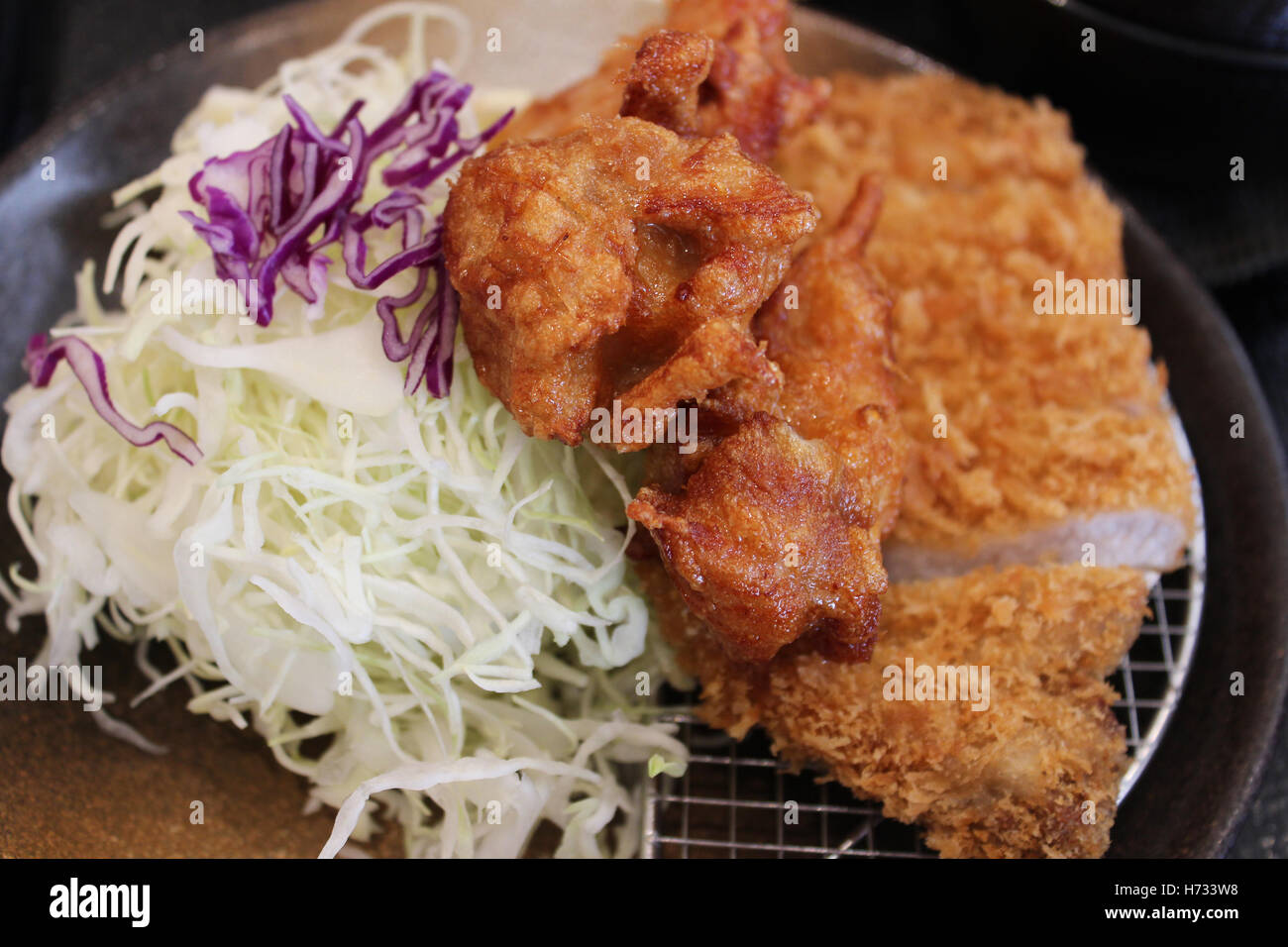 Fried chicken and pork cutlet served with cabbage in the restaurant in Nara, Japan - Stock Image