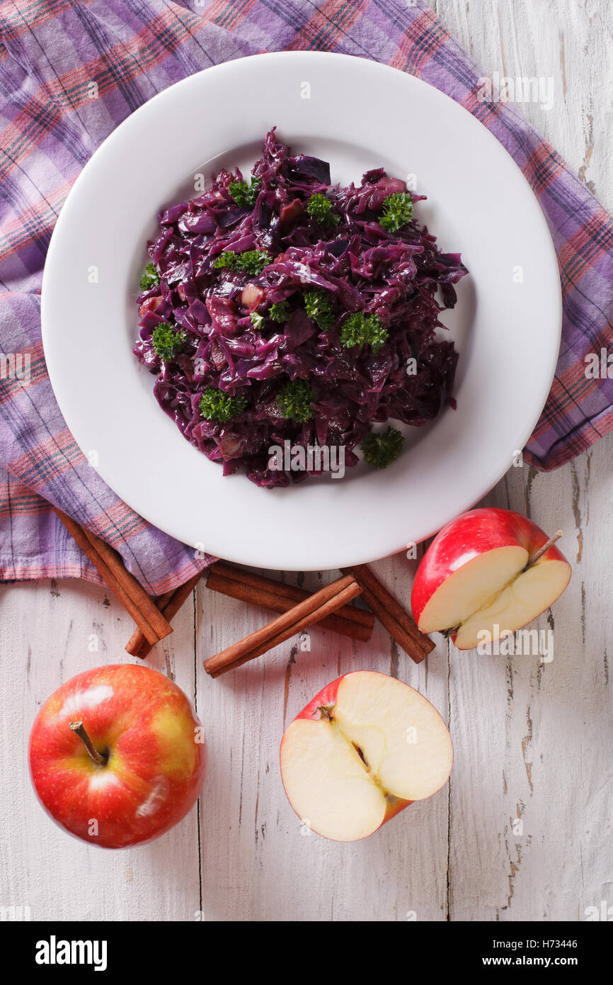 braised red cabbage with apples and cinnamon close-up on the table. Vertical view from above - Stock Image