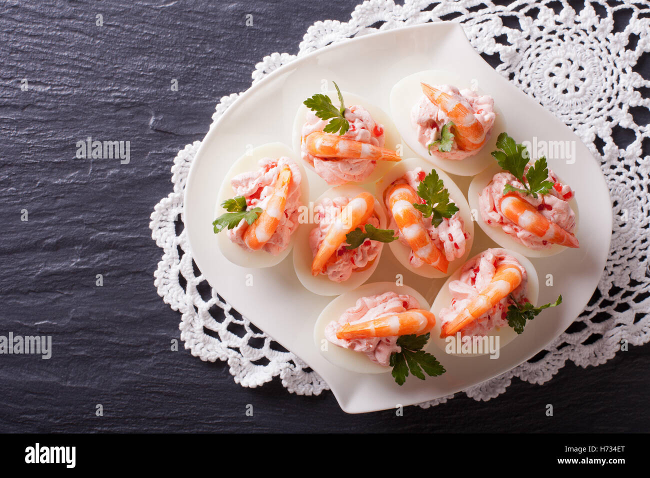 eggs stuffed with shrimp on a plate on the table. horizontal view from above - Stock Image