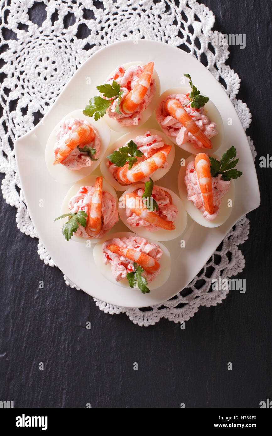 eggs stuffed with shrimp on a plate on the table. vertical view from above - Stock Image