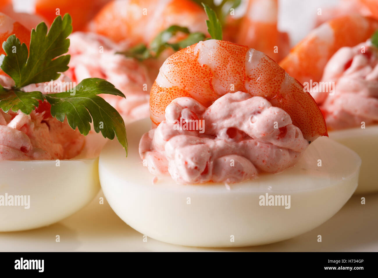 eggs stuffed with shrimp, cheese and caviar macro on a plate. horizontal - Stock Image