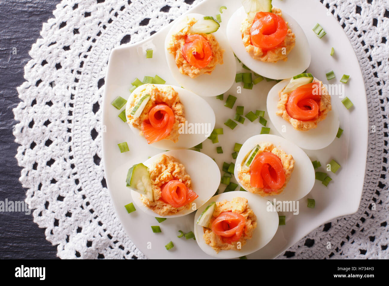 Eggs stuffed with salmon, cheese and cucumber closeup on a table. Horizontal view from above - Stock Image