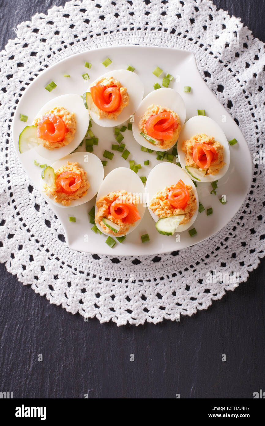 Eggs stuffed with salmon, cheese and cucumber on a table. vertical view from above - Stock Image