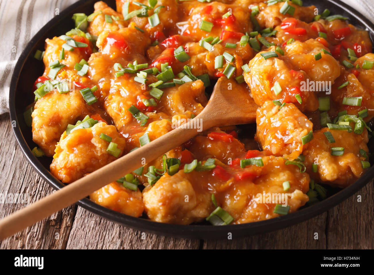 Spicy chicken in orange sauce closeup on a plate. Horizontal - Stock Image