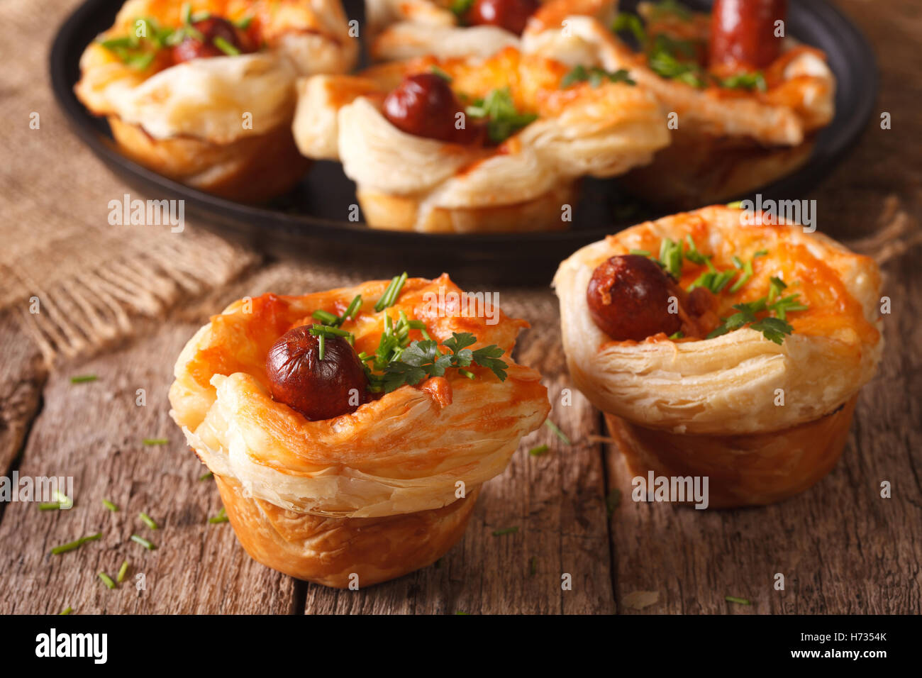 buns of puff pastry with sausage and cheese close-up on the table. Horizontal - Stock Image
