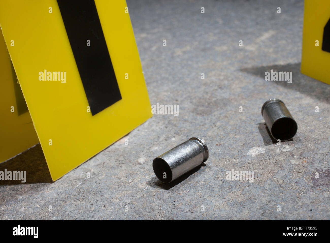 Empty handgun brass on concrete with yellow evidence markers - Stock Image