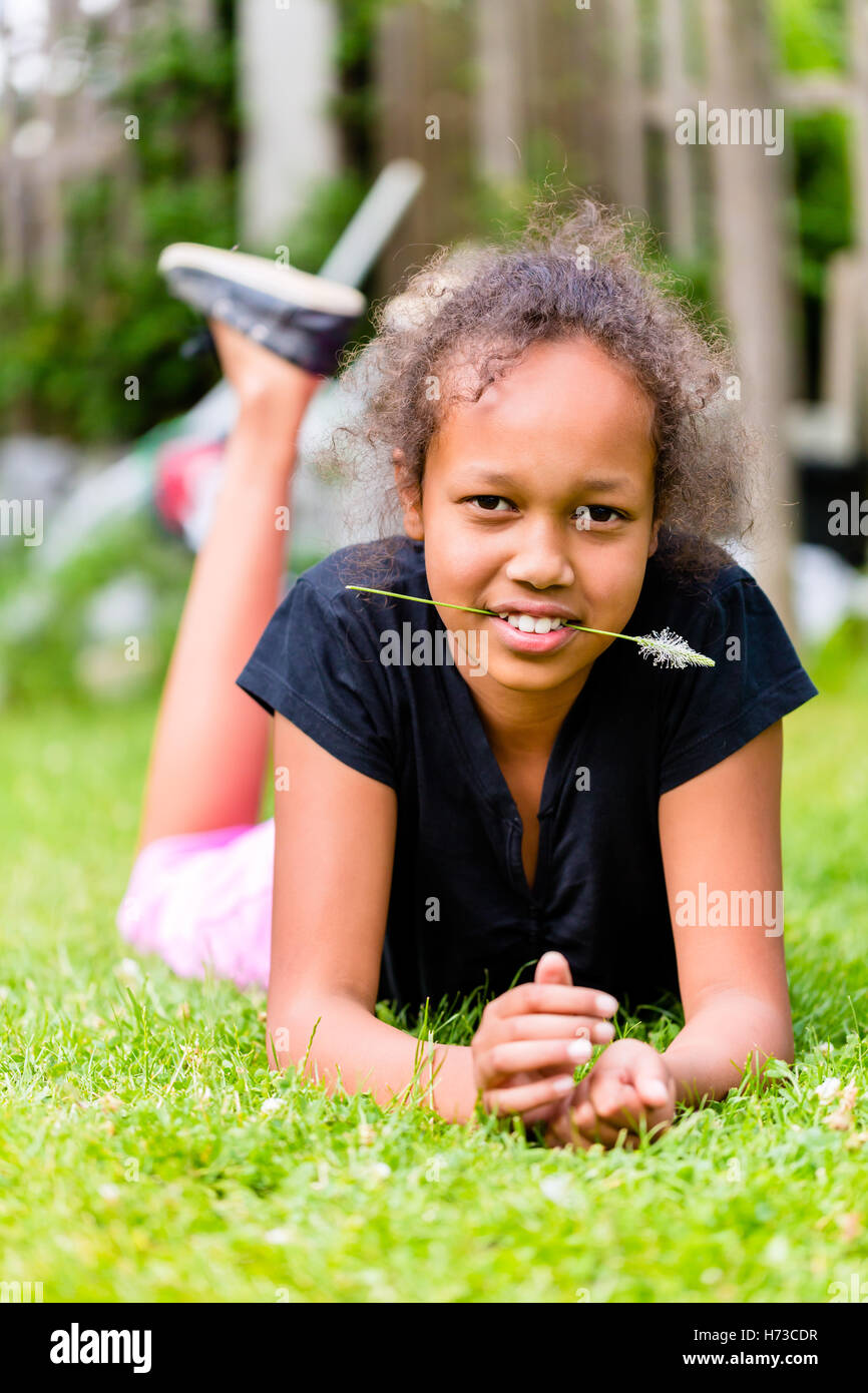 black girl with blade of grass is on meadow - Stock Image