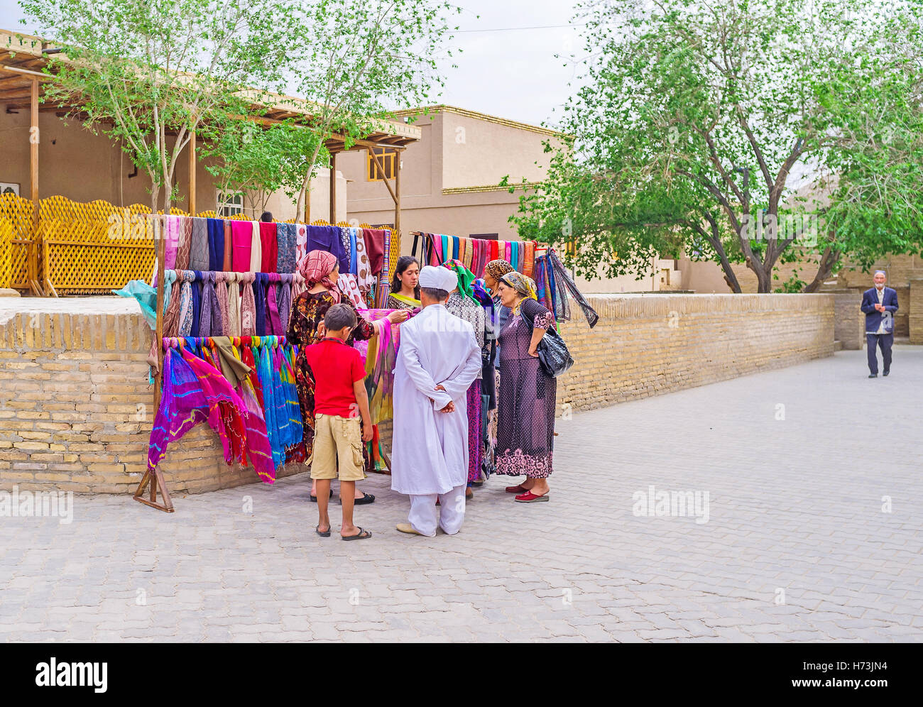 The members of Uzbek family in traditional costumes choose the headclothes at the market stall - Stock Image