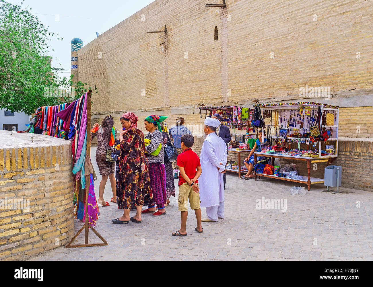 The Uzbek family in traditional costumes choose the gifts at market stall - Stock Image