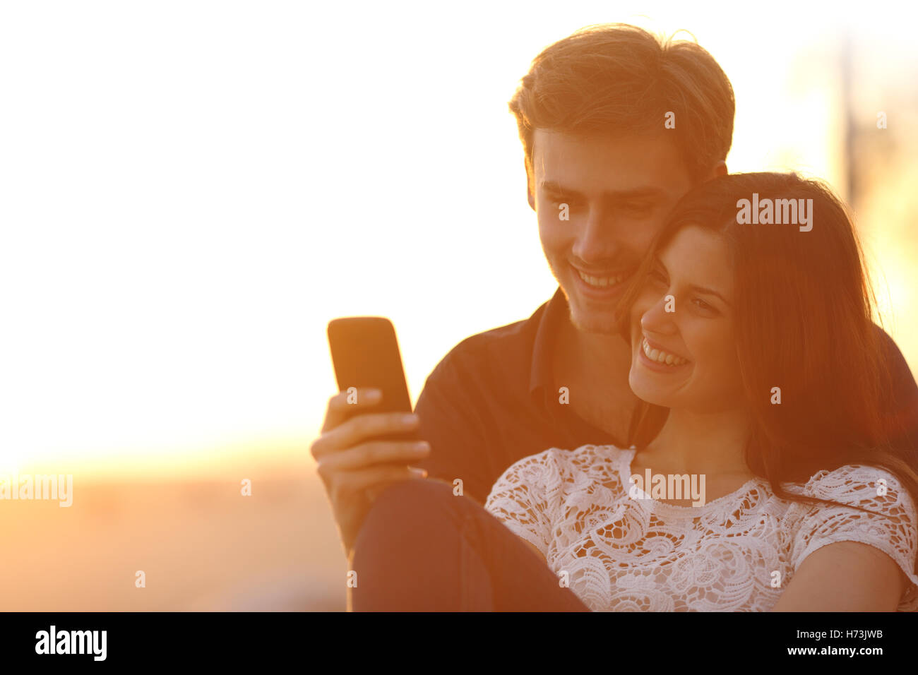 Back light of a couple sharing a smart phone - Stock Image
