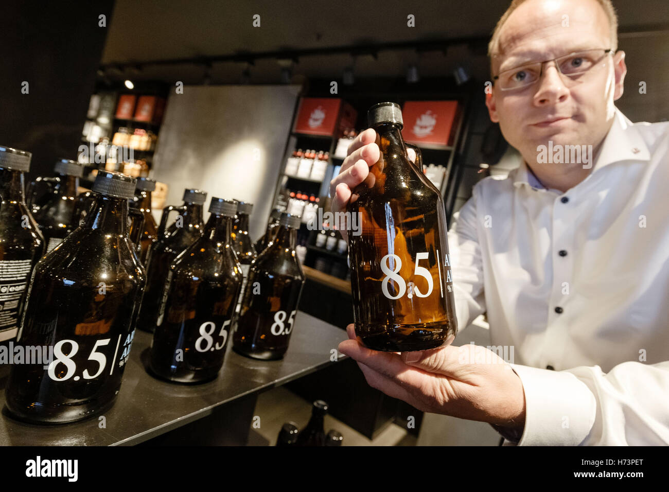 Service personnel Christoph Beyer shows a 'growler' used to let guests choose the beer of their liking to - Stock Image