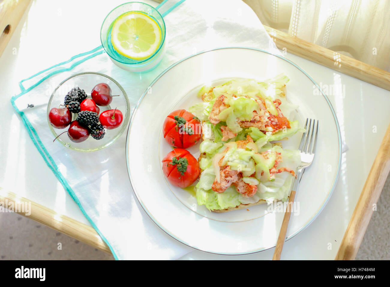 Healthy meal with tomato salad, raspberry and lemonade - Stock Image