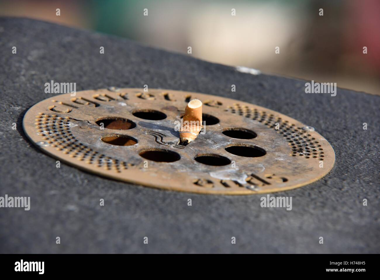 An outdoor street ashtray with a cigarette stub on top UK - Stock Image