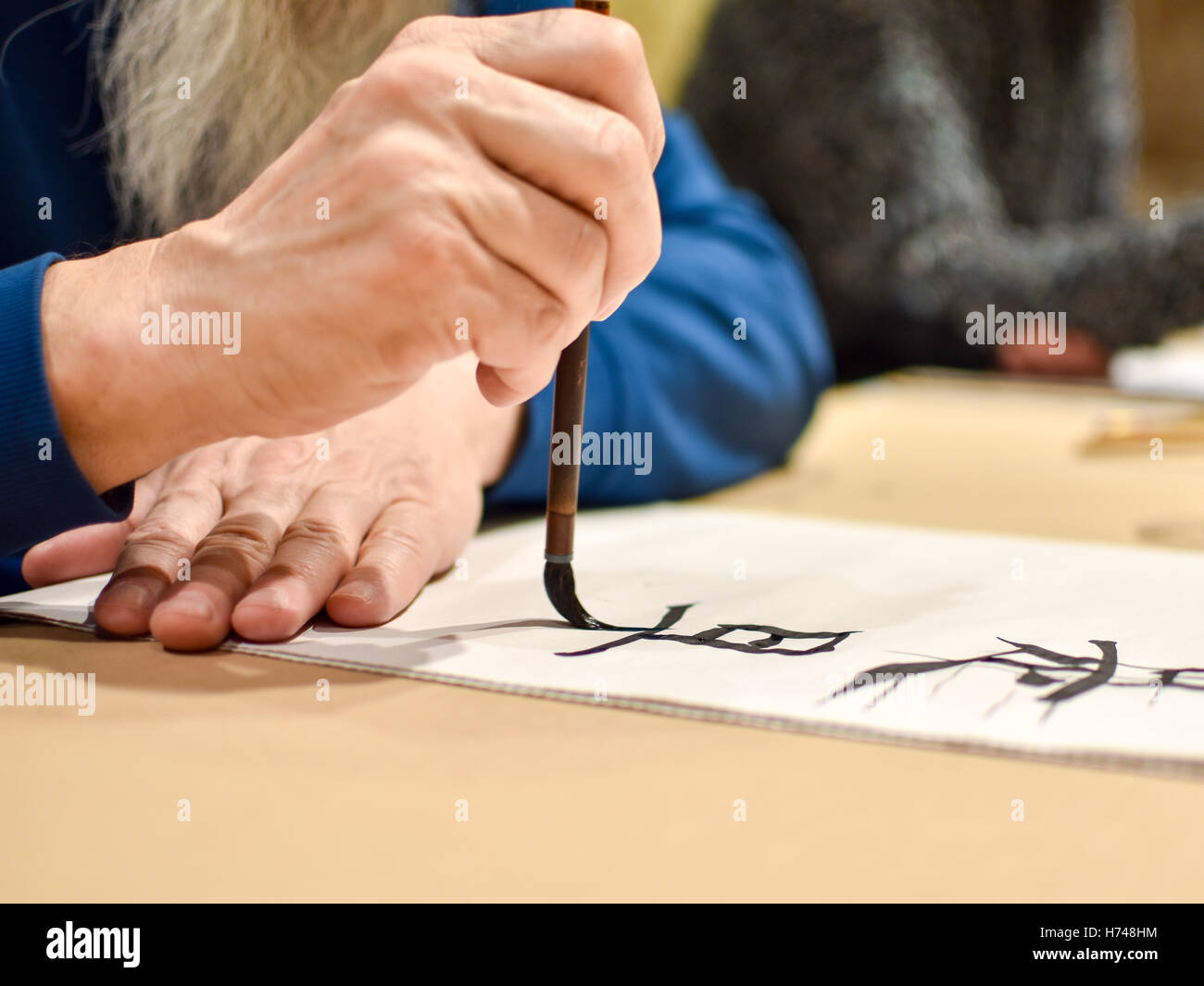 Calligraphy master drawing Chinese hieroglyph with a brush - Stock Image