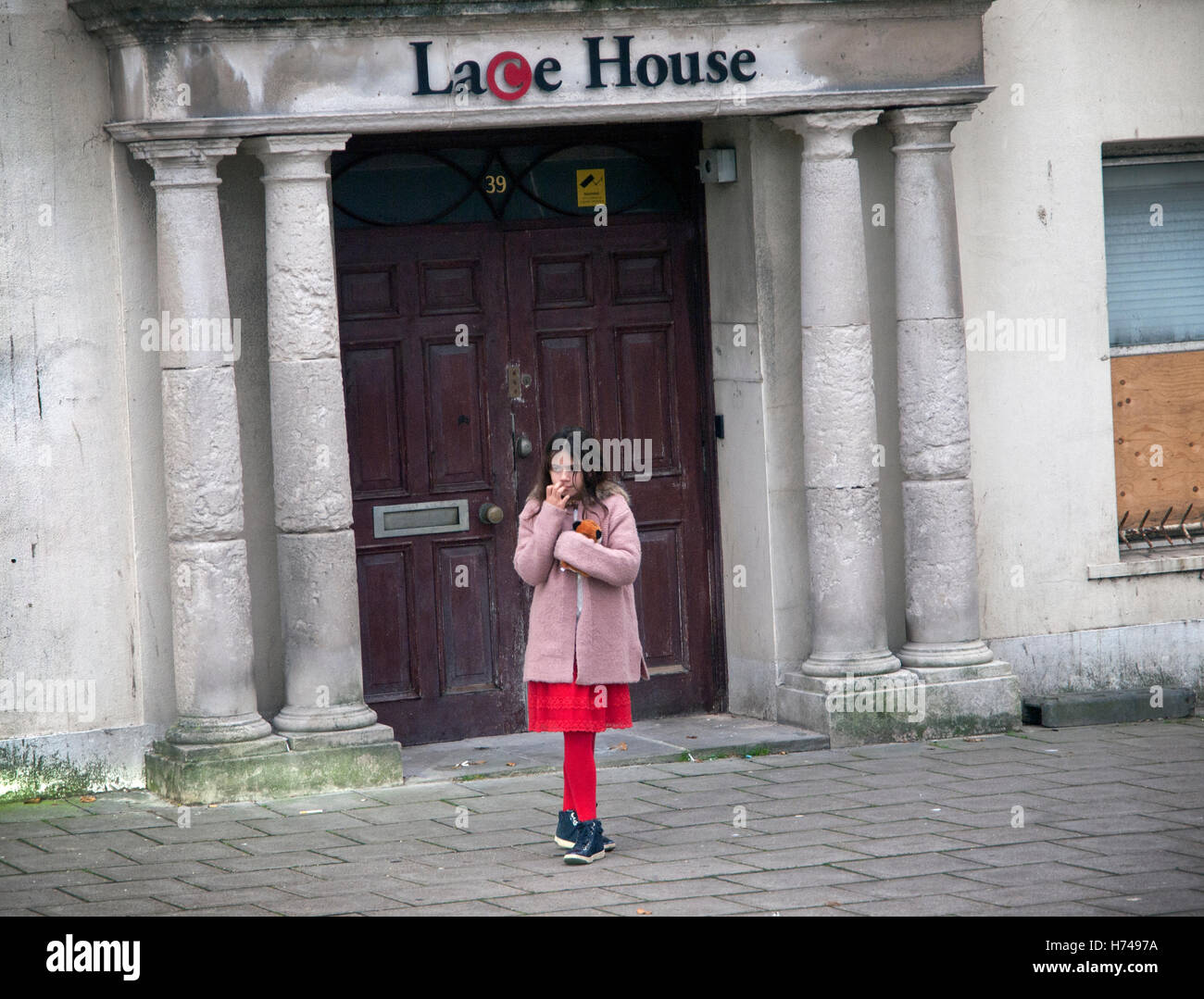 A girl in red tights stands outside Lace House in Brighton - Stock Image