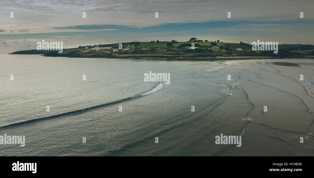 Gentle waves break on the beach as the sun sets on a beautiful island like settlement in the background. Ireland, - Stock Image